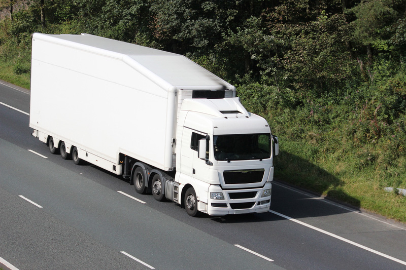 White lorry in the slow lane on a rural three lane motorway.